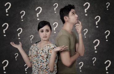 Two people looking confused in front of a blackboard with question marks