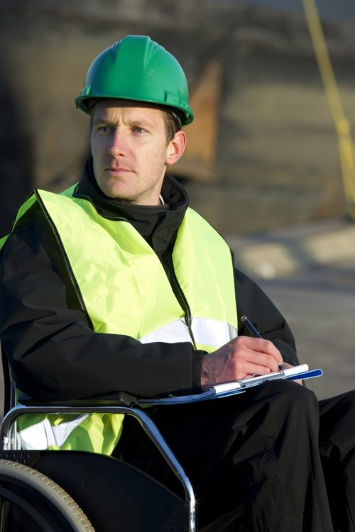 Construction supervisor in wheelchair, wearing safety vest and writing on notepad at construction site