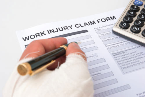 Closeup of a bandaged hand filling out a work injury claim form