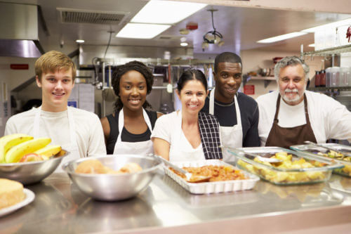 Diverse group of kitchen workers standing behind a buffet of food