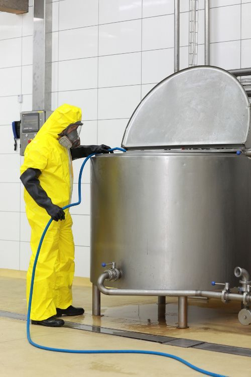 A food chemical safety image of a worker cleaning equipment.