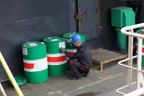 A food chemical safety image of a person inspecting containers.