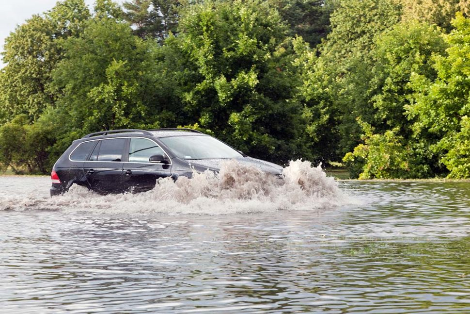 Car driving into flood