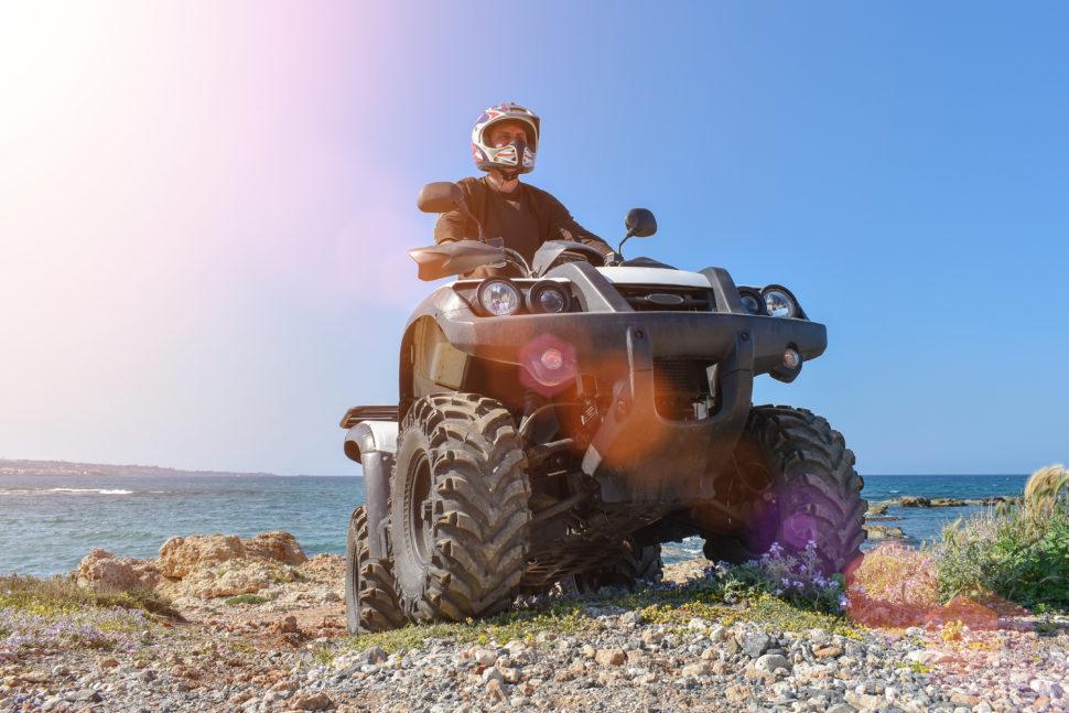 A man is driving an ATV on a beach.