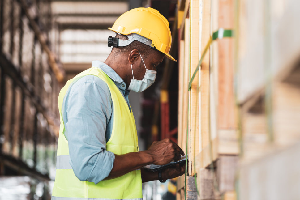 African American man working in a warehouse wearing PPE