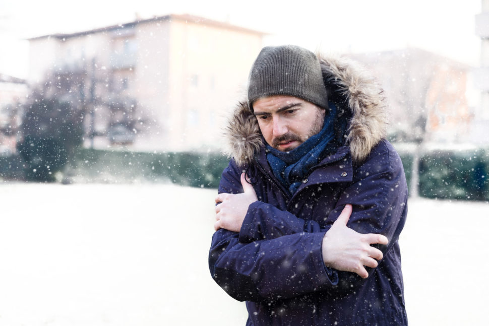 A man shivers in snowy conditions