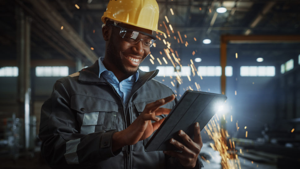 man in factory holds ipad