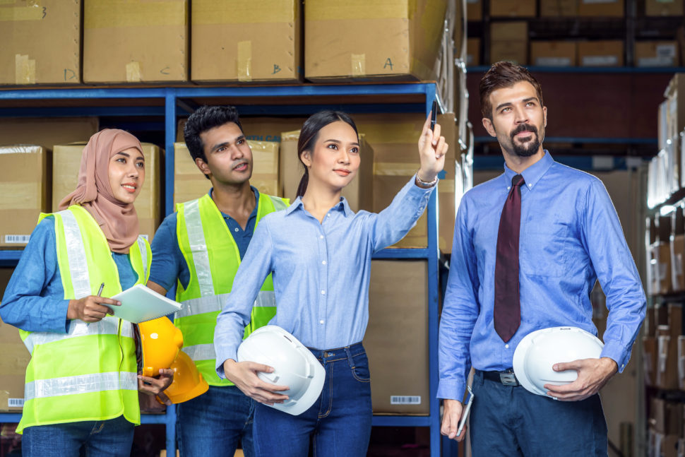 woman hosts meeting with employees in warehouse