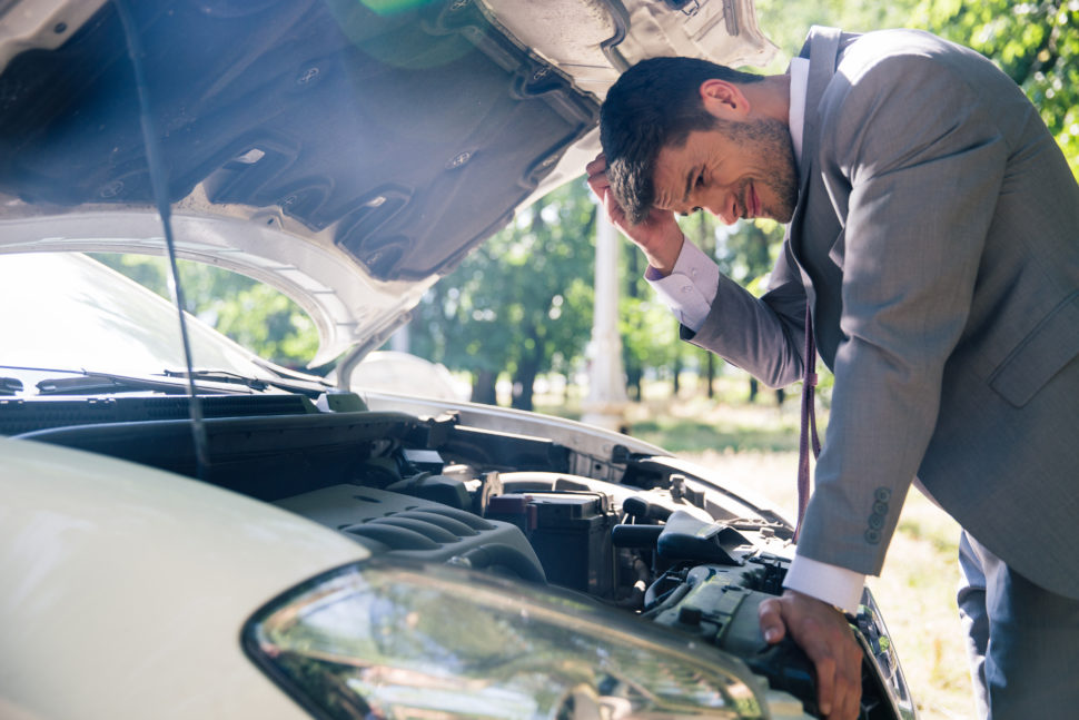 man looking under hood of car