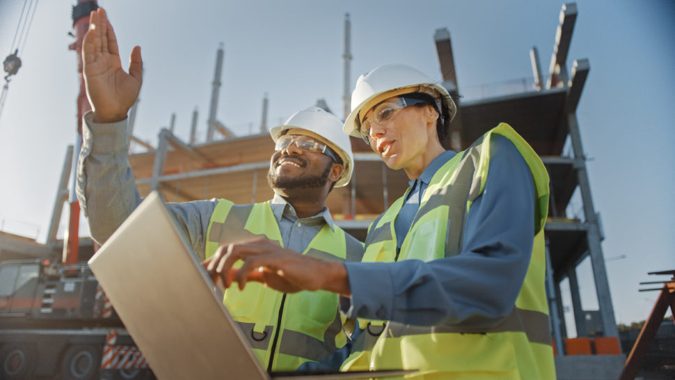 Two workers discussing over an iPad on jobsite