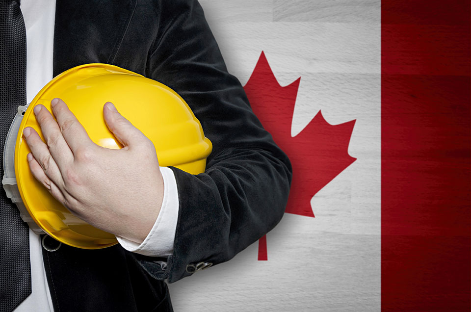 Canadian employee holding hard hat in front of Canadian flag