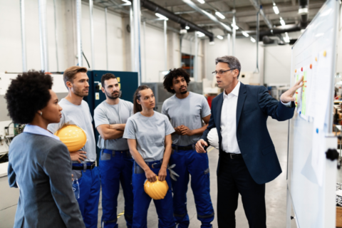 Employees having a safety meeting inside a plant