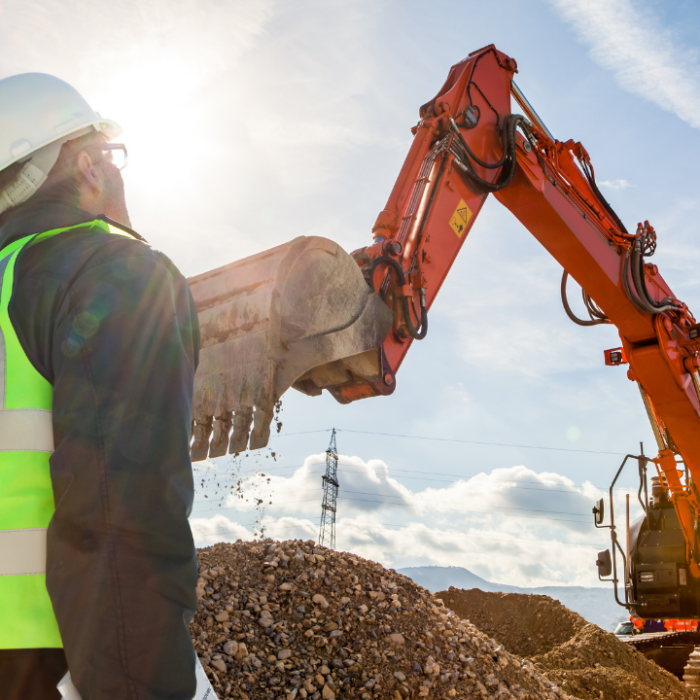 Construction worker inspecting machinery operation